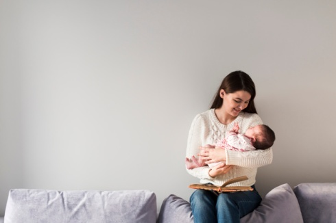 woman-with-book-holding-little-baby_23-2147778626